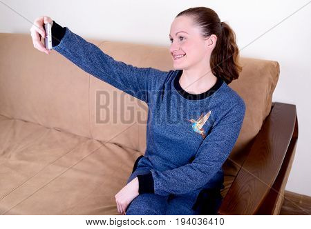 Beautiful Young Happy Woman Sitting On Sofa, Using Smartphone And Texting. Relaxing On The Couch At