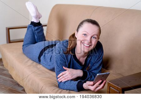 Beautiful Young Smiling Woman Lying On Sofa, Using Smartphone And Texting. Relaxing On The Couch At