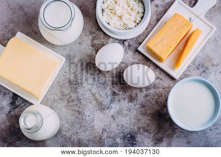 Top view of Fresh dairy product on kitchen table. Cheese eggs milk cottage cheese yogurt cream and butter. Copy space
