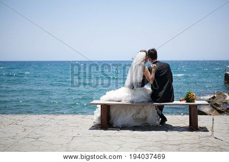 Couple smiling and embracing near wedding arch on beach. Honeymoon on sea or ocean.