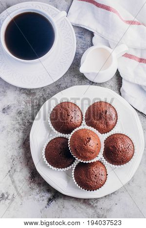 Homemade chocolate muffins and white cup of coffee on gray table background. Mini cakes for breakfast. Top view with copy space