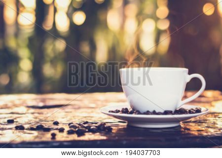 Hot coffee in the cup and coffee beans on old wood table - soft and blur effect