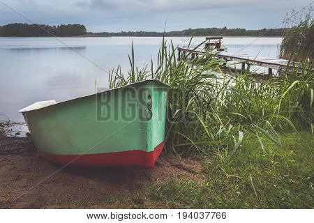 Fisherman's boat at rainy evening at Masuria lake. In background there is wet bridge with fishing poles.