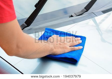 A man hand cleaning car bonnet with microfiber cloth