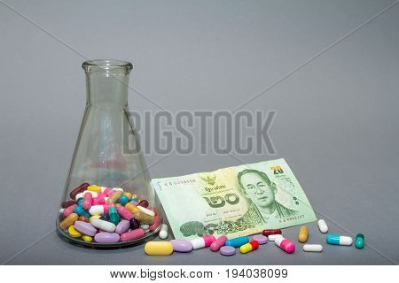 Medical pills in different colors and money. Colorful pills on a gray background.