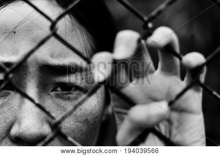 Depressed Woman Standing Behind A Fence, Hand Grabs Steel Mesh Cage