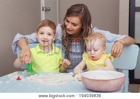 Group portrait of young white Caucasian mother with children playing kinetic sand together at home. Early creativity brain development concept. Lifestyle family activity.