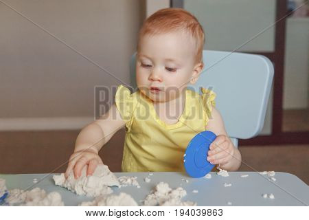 Portrait of funny cute white Caucasian baby playing kinetic sand indoors at kindergarden. Early creativity brain development concept. Children home activity. Fine motor skills.