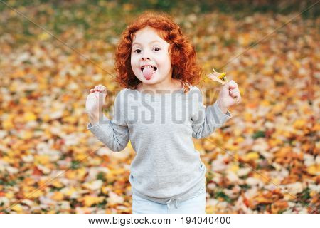Portrait of cute adorable little red-haired Caucasian girl child making funny silly faces showing tongue in autumn fall park outside playing having fun lifestyle childhood
