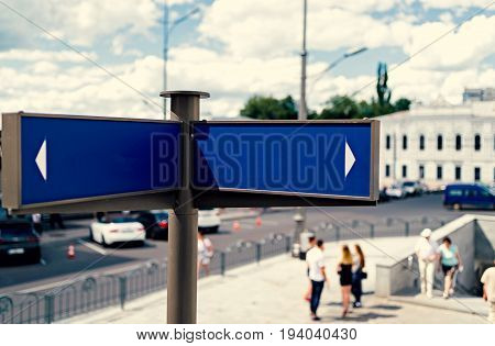 Blank Blue Street Signs With City And People In Blur On Background, Free Space For Text. Blank Blue
