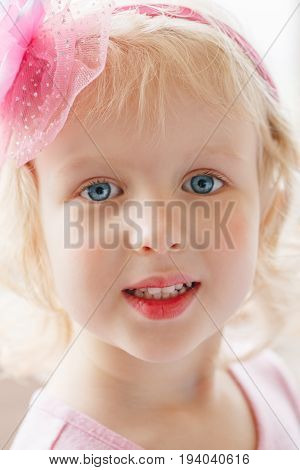 Closeup portrait of cute adorable blonde white Caucasian smiling baby girl with large blue eyes wearing pink headband looking in camera