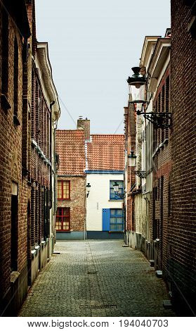 Obsolete Narrow Street with Multi Colored Old Houses and Street Lantern in Cloudy Day Outdoors. Bruges Belgium