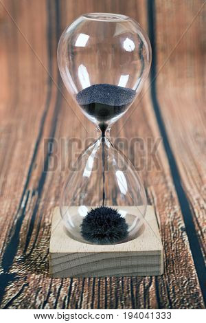 Hourglass iron sand measuring the passing time in a countdown to a deadlineon wooden background