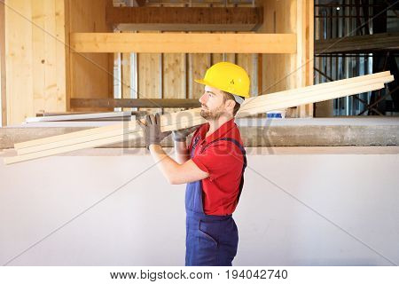 Carpenter worker holding some wooden boards in building site