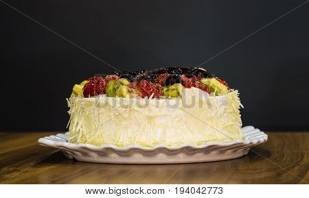 Delicious Creamy Whole White Chocolate Cake With Fruits On Top On Dark Background