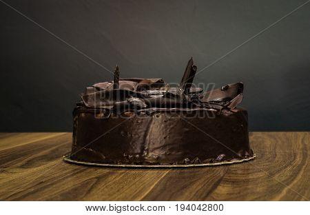 Delicious Creamy Whole Dark Chocolate Cake On Dark Background