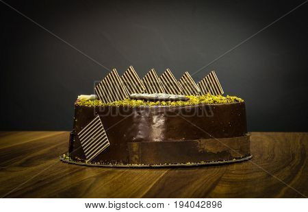 Delicious Creamy Whole Dark Chocolate Cake With Pistachio On Topping On Dark Background