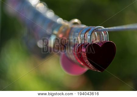 Red Lock in hart shape on rope bridge