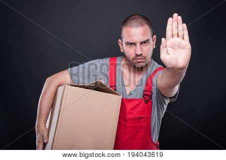Serious Mover Man Holding Box Showing Stop Gesture