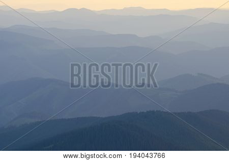 Sunlit mountains ranges. Evening or morning scene. Mountain covered with green forest in foreground.