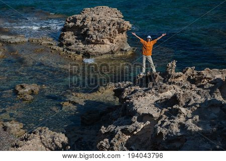 Woman with outstretched hands situated on rock . Blue and clear sea in background.