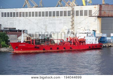 St. Petersburg, Russia - June 25 2017: Red oil tank cargo ship in the port. Containers with goods are loaded / unloaded on a commercial vessel using a crane in the harbor of city. Business transport concept