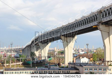 Bridge over industrial area trade port with railway wagons with cranes and navigable channel of the Western high-speed diameter, a toll motorway crosses the entire city, linking the North and South