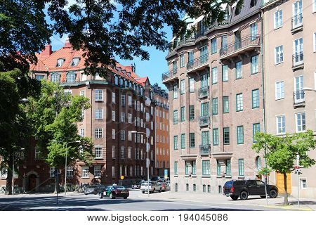 Stockholm, Sweden- 27 Jun 2017: view of the street with a classic Swedish homes, Scandinavian style of brown brick and grey stone, the cars are parked on the street, the center of the capital.