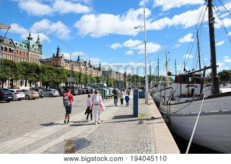 Stockholm, Sweden- 27 Jun 2017: Views of the scenic waterfront in the city center with tourists and pedestrians in background of yachts and historic buildings Scandinavian capital on blue sunny sky