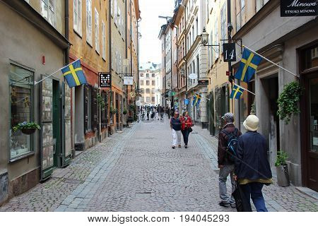 Stockholm, Sweden- 27 Jun 2017: narrow little tourist street in the old town of Gamla Stan centre of the scandinavian city with cozy cafes, souvenir shops and pedestrians. Hung Swedish flags