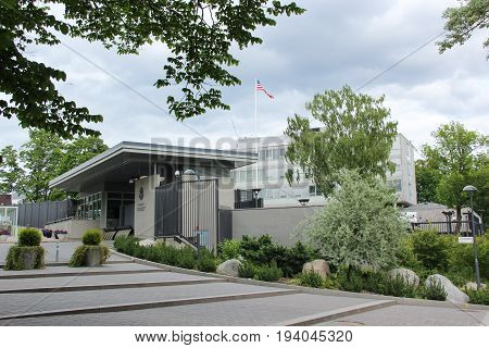 Stockholm, Sweden- 27 Jun 2017: The building of the American Embassy with a flying flag against the cloudy grey of the Northern sky and green trees Scandinavian capital.