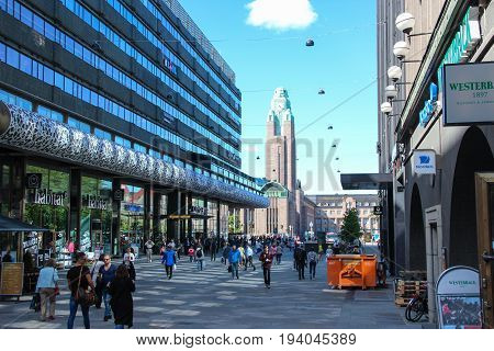Helsinki, Finland - 28 Jun 2017: Day view of the city: the main railroad station with the clock tower and street with shopping complex on the daylight