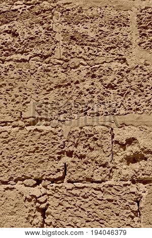 rough porous texture of stone bricks of an old and ancient wall of color sepia