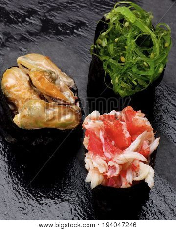Various Japanese Sushi Gunkan Rolled Up in Nigiri with Seaweed Shrimps and Mussels in Sauce closeup on Wet Slate background. Focus on Foreground
