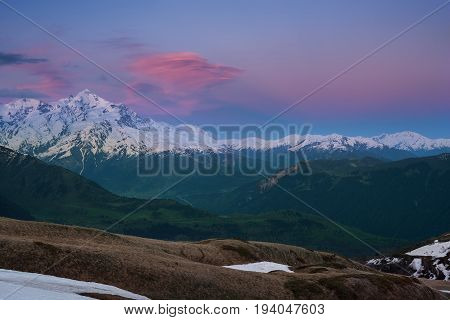 Colorful Red Clouds Float Over Beautiful Snow-capped Peak