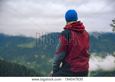 Man Adventurer Is Standing In The Mountains And Looking At The Heavy Clouds