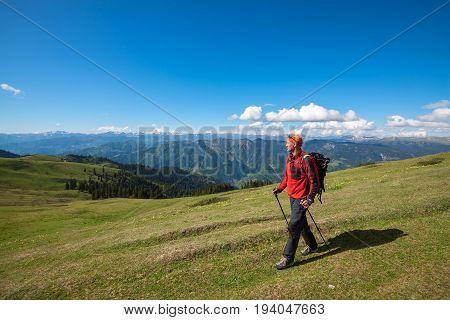 Happy Hiker Walks Along Alpine Meadow