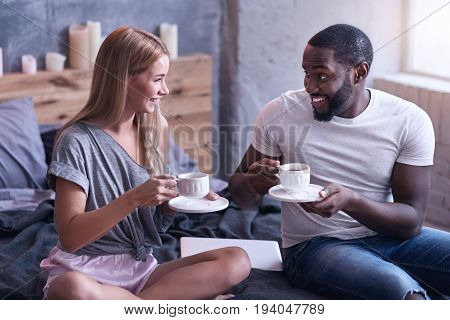 Happiness around us. Positive delighted international couple sitting in the bedroom and drinking tea while enjoying weekend and expressing positive feelings