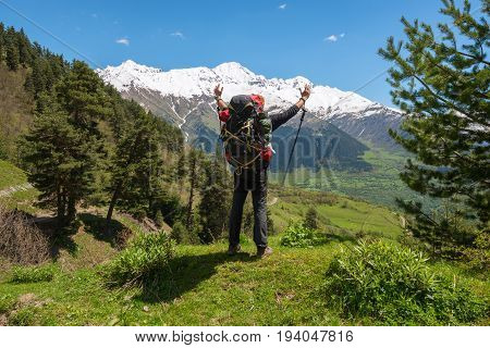 Joyful Man Traveler With Open Arms Stands On The Alpine Meadow