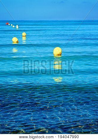 Yellow Boundary Mark Floats on Ripple Sea Water Surface on Blue Sky Horizon Outdoors