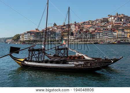 Traditional Rabelo Boat on the Bank of the River Douro and Colorful Facades of Typical Houses- Porto Portugal