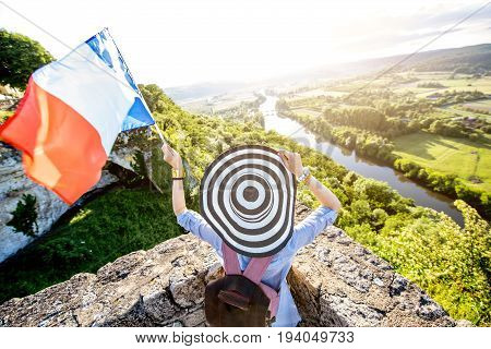 Young woman tourist with french flag enjoying sunset view on the beautiful landscape with Dordogne river in France