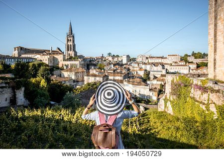 Young woman tourist enjoying beautiful cityscape view on Saint Emilion village in Bordeaux region in France