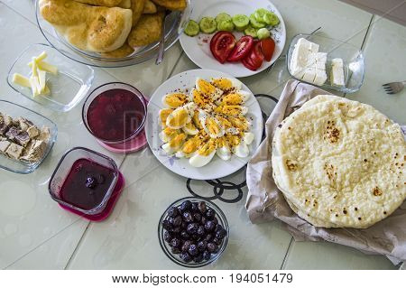 Traditional Turkish breakfast table with tea, jam, fresh bread, cheese, green onions, parsley, tomatoes, cucumber pictures
