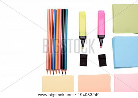 Colored Pencils And Markers With Paper For Writing Isolated On White Background