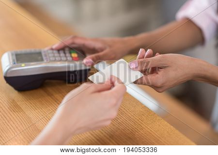 partial view of woman giving credit card to waitress for payment in cafe