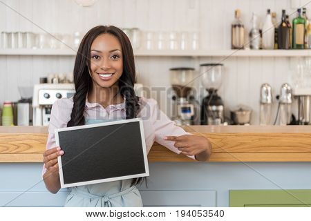 afro-american waitress pointing at empty board and looking at camera while standing at cafe