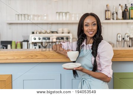 attractive african american waitress in apron drinking coffee and looking at camera at cafe