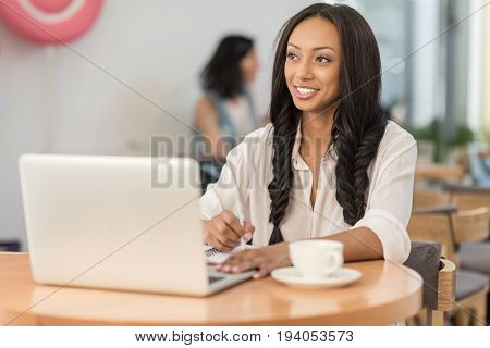 young attractive african american businesswoman using laptop while sitting at cafe