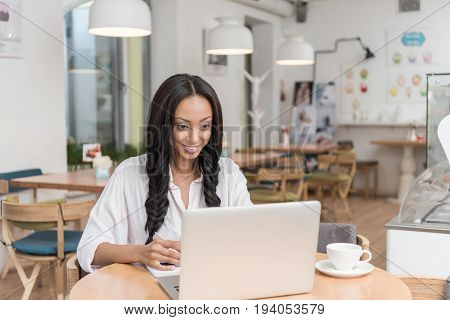 young attractive african american smiling businesswoman working on laptop while sitting at cafe